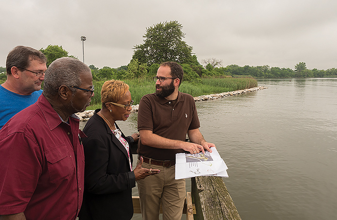 Isaac Hametz (right), of the landscape design firm Mahan Rykiel Associates, reviews park upgrade plans with (from left) Doug Myers of the Chesapeake Bay Foundation and Larry Bannerman and Gloria Nelson of the Turner Station Conservation Teams. (Dave Harp)